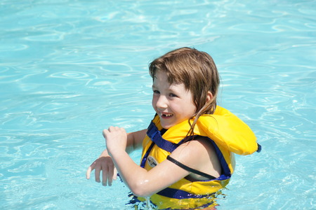 lifejacket: Little girl with lifejacket in pool. Stock Photo