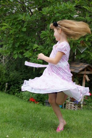 twirling: Young girl twirling with pink dress.