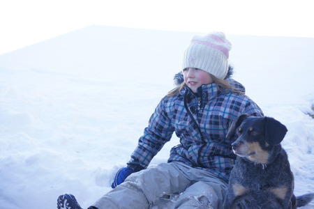 Little girl and dog, snow background. Stock Photo