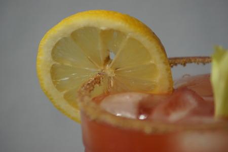 rimmed: Close up of lemon on a celery salt rimmed glass.