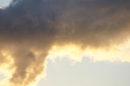 Sunlight peeking threw the bottom of storm brewing soon darkening clouds.