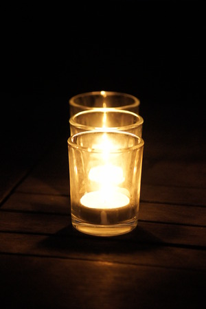 Three lit candles lined up in a row, placed upon a wooden table in the dark.