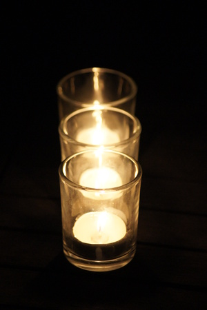 Three flickering candles light up the darkness of night outdoors.