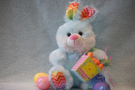 Sweet stuffed blue Easter bunny sits with his basket of carrots with eggs around him. Reklamní fotografie