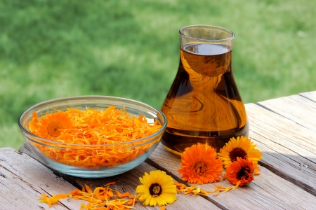 Calendula flower petals and oil extract in a glass jug photo