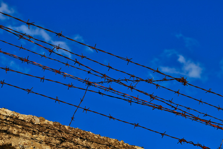 atop: Old rusty barbed wire fence atop concrete wall Stock Photo