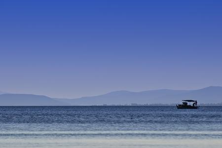 encrespado: Barco de pesca en aguas picadas shlight de monta�as distantes y cielo azul