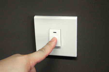 switch on the light: Cierre de dedo de apagar el interruptor de luz en la pared Foto de archivo