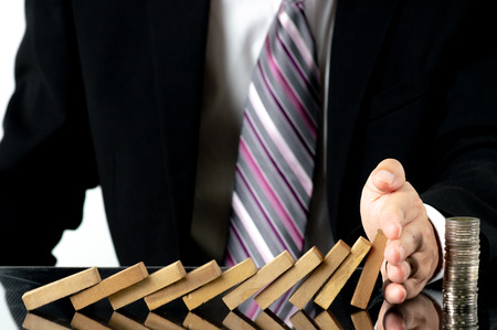 Close-up Businessman hand stopping wooden blocks from falling on stacked coins over desk. Risk management concept.