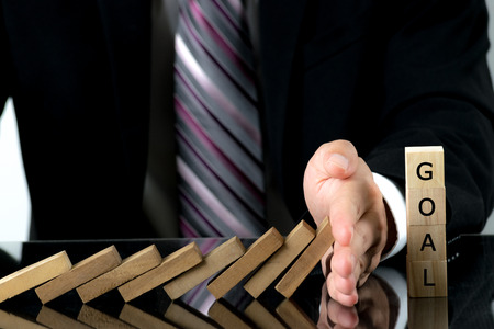 Businessman hand stopping the domino wooden effect  to wooden cubes with text GOAL for business success. Risk management concept.