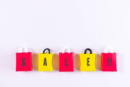 白いテーブル、トップビューの上にブラックフライデー紙のショッピングバッグ。掘り出し物や低価格、季節割引やプロモーションを探している小売消費者や買い物客についての概念。