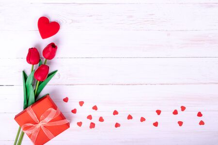 Red tulips bouquet and a gift on white wooden background, top view and copy space for card and advertiser