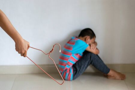 Domestic violence: female hand with Hanger on the background of kid. Abused child, aggression in the family.