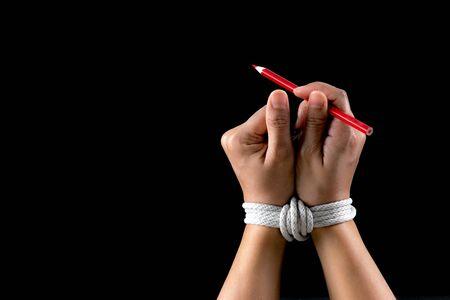 Hand- und Rotstift mit Seil gebunden, die die Idee der Presse- oder Meinungsfreiheit auf dunklem Hintergrund darstellen. Konzept zum Welttag der Pressefreiheit. Standard-Bild