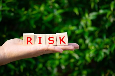 Close-up Womans hand holding wooden blocks text RISK over tree background. Risk management concept.