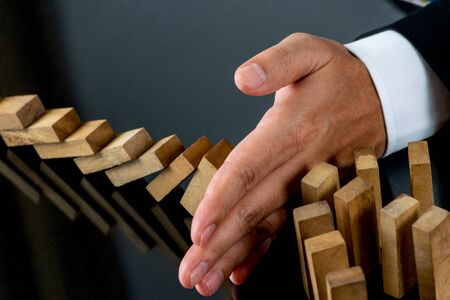 Businessman hand stopping the domino wooden effect concept for business. Risk management concept. Foto de archivo