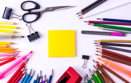 Backpack with different colorful stationery on white table background. Back to school concept.