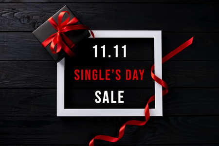 Online shopping of China, 11.11 singles day sale concept. Top view of white picture frame with black gift box on black wooden background with copy space for text 11.11 singles day sale.