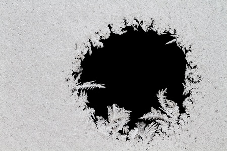 Ice crystals on glass with a circle isolated on black. Stock Photo