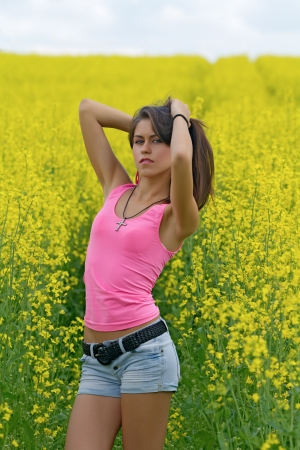 non urban 1: girl spreading her arms in the middle of a rape  canola  field with blue cloudy sky
