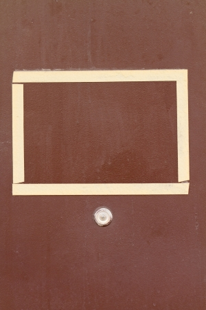 peephole: peephole and frame for announcements of masking tape on the door Stock Photo