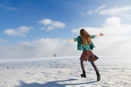 Girl jogging in snowy field photo
