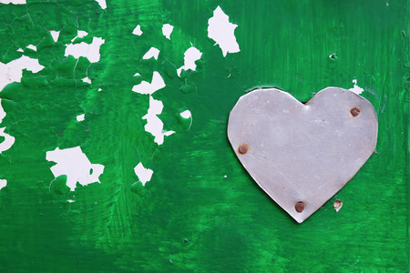 hobnail: metal heart shape on green painted surface Stock Photo