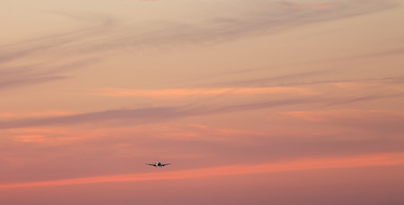 jet airplane in silhouette landing off at sunset Stock Photo