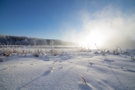 Winter landscape on the river, the rising sun shines through the mist