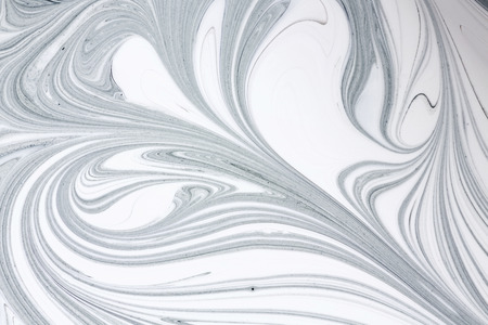 Mix of a white and black paint, closeup.