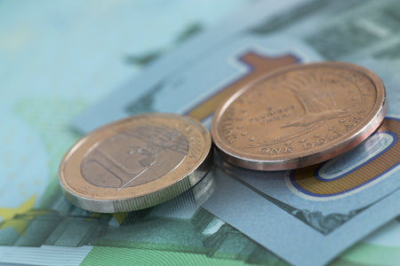 Euro dollars one coins on the background of hundred  dollars and hundred euros