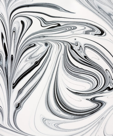 White and black paint mixing together creating shapes.