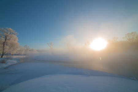 Winter landscape, sunrise over an unfrozen river