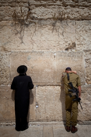 soldier and orthodox jew at the wailing wall