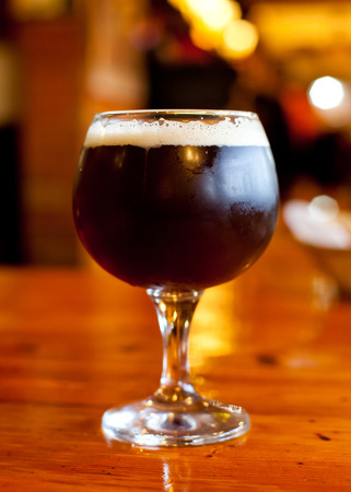 Glass of dark Belgian beer on a wooden table