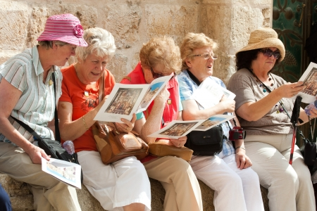 guided: group of mature female tourists, sitting outside the church of the holy sepulchre, holding  brochures