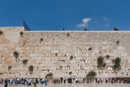 People pray at the western wall, Jerusalem, Israel wide shot with blue sky