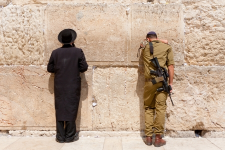 hasid: Soldier and Orthodox jews pray at the wailing wall  Jerusalem with people