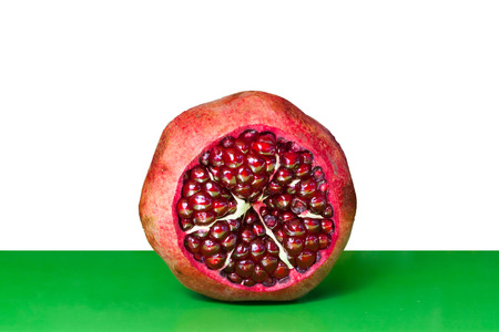 reg: Open Pomegranate with seeds on white and green  Stock Photo