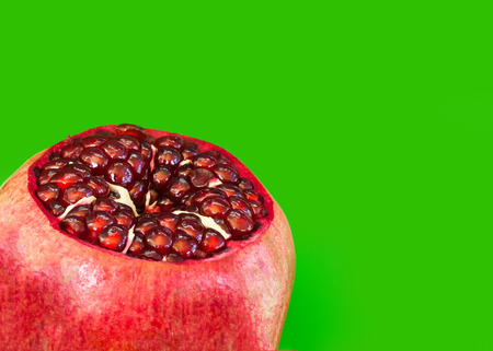 reg: Open Pomegranate with seeds on green
