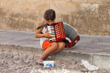 tocando musica: joven ni�o mendigo, la reproducci�n de m�sica en las calles de Atenas, Grecia, con la gente