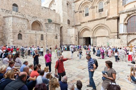 tour guide: Grupo de turistas, sentado fuera de la Iglesia del Santo Sepulcro durante una visita guiada Editorial