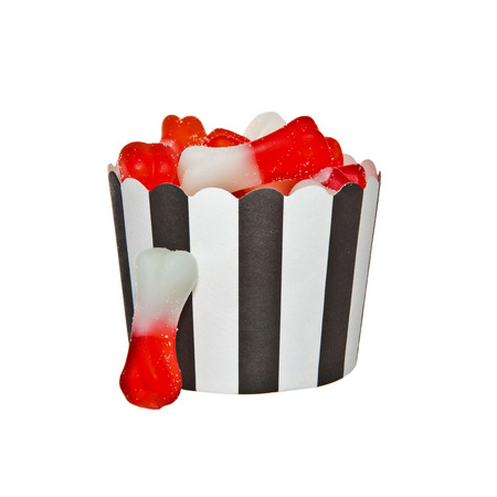 artificially: Bone shaped Jelly candies and a black and white paper cup