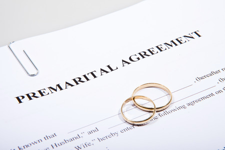 Prenuptial agreement form with two gold wedding rings Standard-Bild