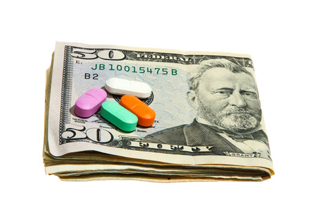 obama care: Pills and Dollar notes isolated on white