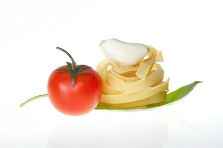 Arrangement of Tagliatelle pasta cherry tomato garlic and basil photo