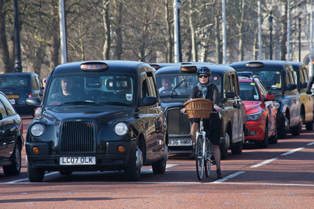 hackney carriage: Row of black london cabs in a traffic stop with a female cyclist at Mall street next to Buckingham Palace Editorial