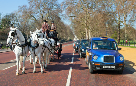 Traditional horse carriage with British gentleman next to a classic London cab in the roads of london