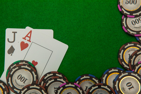 Jack and ace blackjack cards with chips on green background Stock Photo