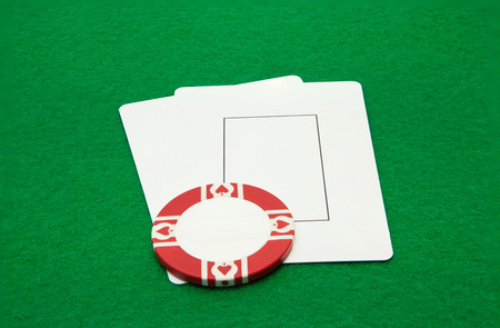Two blank play cards with casino chip on green background photo